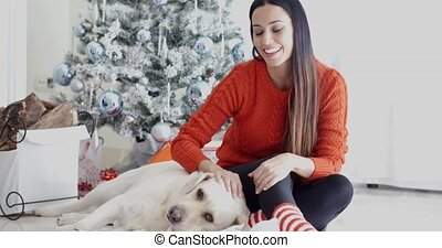 Laughing young woman with her dog at Christmas sitting...