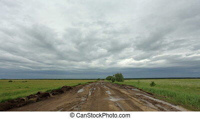 Movement of clouds over a dirt road. Lubinsky District, Omsk...
