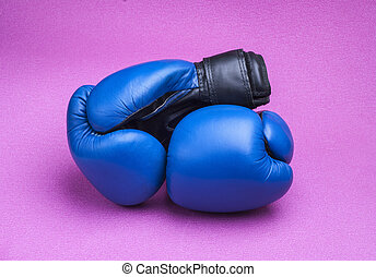 boxing gloves - two black boxing legs lie on a blue mat