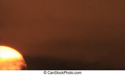 Sun disk close-up rises - Sunrise in smoke clouds bright big...