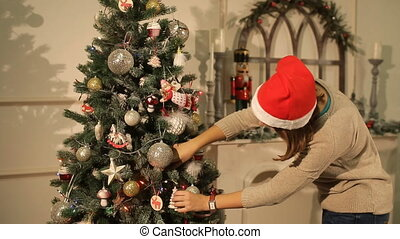 girl hangs on a Christmas tree ball - girl hangs on a...