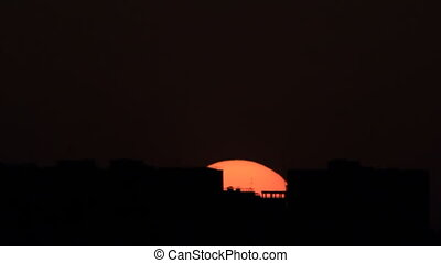 Sunrise in town - Sun's disk above town apartments houses...