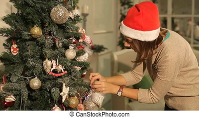 girl hangs on a Christmas tree ball