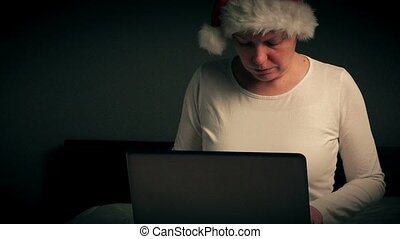 Lonely woman browsing internet on Christmas eve, adult...