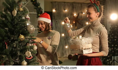 two friends decorate a Christmas tree