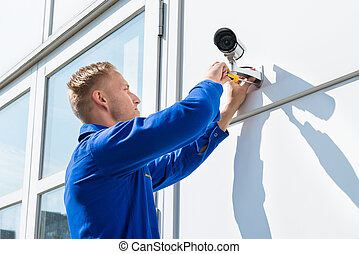 Technician Fixing Camera On Wall With Screwdriver