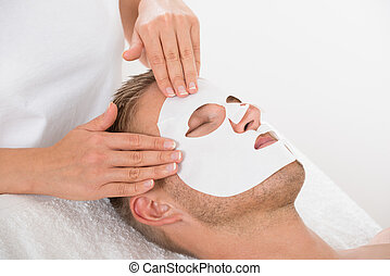 Young Man In Spa Salon With Facial Mask