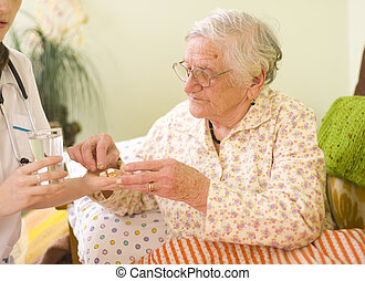 Medications for an old woman - A young doctor giving...