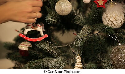 girl hangs on a beautiful Christmas tree toy
