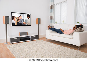 Woman Falling Asleep While Watching Television - Young...