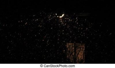 Night snowfall on street lamp lights - Night snowfall in...