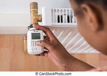 Woman Adjusting Temperature On Thermostat - Close-up Of A...