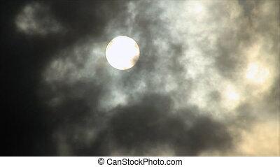 Sun disk behind backlit clouds