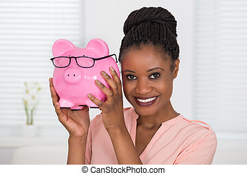 Woman Holding Piggybank - Close-up Of Smiling Young African...