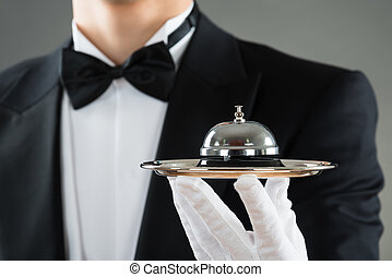 Midsection Of Waiter Holding Service Bell In Plate -...