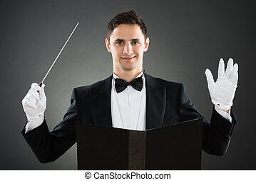 Smiling Music Conductor Holding Baton - Portrait of smiling...