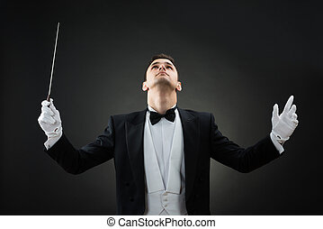 Music Conductor Looking Up While Holding Baton - Young male...