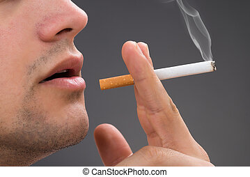 Man Smoking Against Gray Background - Cropped image of man...