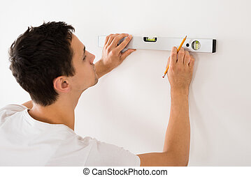 Man Using Spirit Level On White Wall