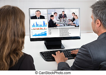Two Businesspeople Participating In Video Conference - Two...