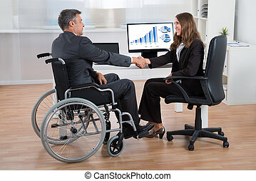 Businesswoman Shaking Hands With Disabled Businessman -...