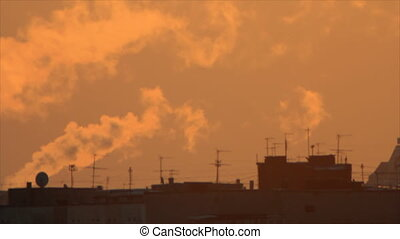 Backlit smoke over town building silhouettes
