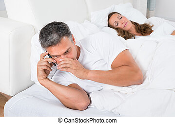 Man Busy On Phone While Woman Sleeping - Man Talking On...