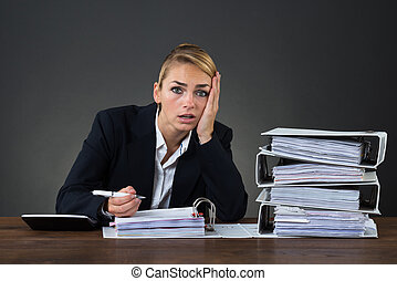 Stressed Businesswoman Looking At Folders While Working At...