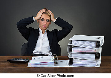 Tired Businesswoman With Hands On Head At Desk - Tired...