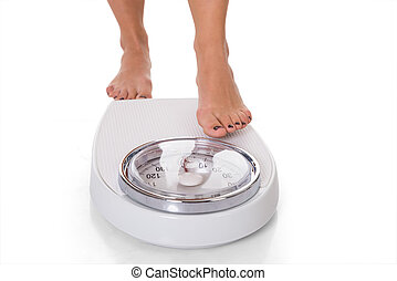 Low Section Of Woman Standing On Weighing Scale - Low...