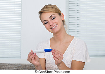 Woman Looking At Pregnancy Result At Home - Happy young...