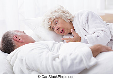 Mature marriage arguing in bed
