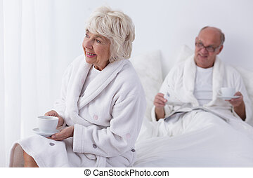 Morning coffee in bed - Photo of elderly couple having...