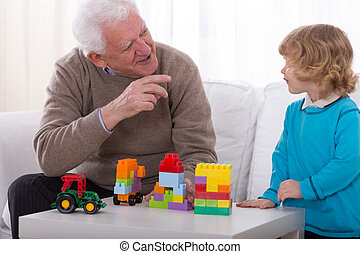 Joking with grandson - Happy grandfather joking with his...