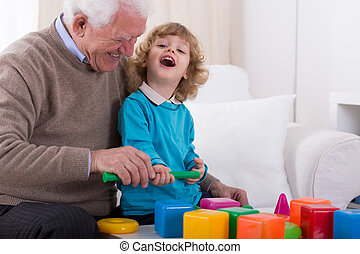 Laughing with granddad - Happy small boy laughing with his...