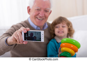 Doing a photo - Smiling grandfather doing photo with his...