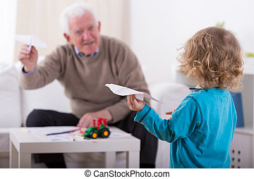 Grandson and paper airplanes - Grandfather and grandson and...