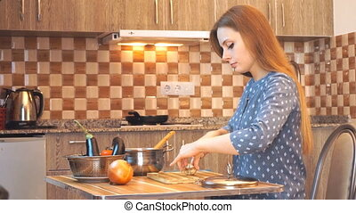 Healthy food lifestyle: beautiful woman casually cooking, cutting vegetables at kitchen. Medium shot, handheld.