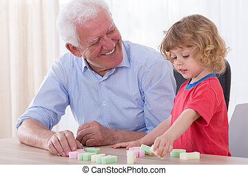 Setting the letters - Smiling granddad setting the letters...