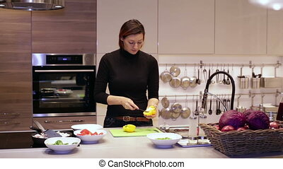 Woman cuts knife yellow pepper on the Board - A woman with a...