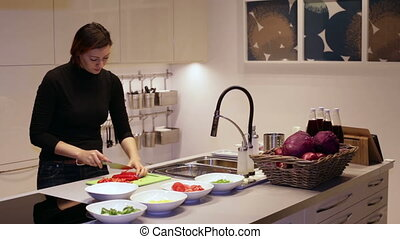 Woman cuts knife red pepper on the Board - A woman with a...
