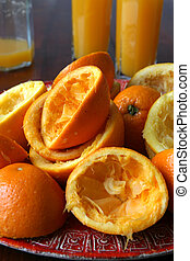 Squeezed oranges and fresh orange juice - Plate with...