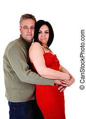 Couple hugging. - An middle age couple, she in an red dress...