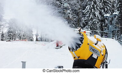 Snow machine gun on a ski slope. - Yellow snow cannon stands...
