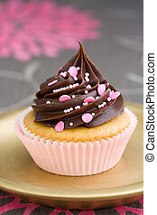 Pink chocolate cupcake served on a gold plate