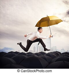 Stand out from the crowd - Man with yellow umbrella runs on...