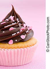 Pink chocolate cupcake against a pink background