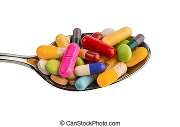 many tablets on spoon - many colorful pills on a spoon photo...