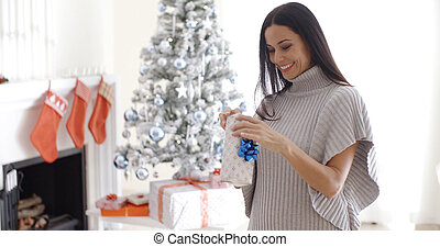 Pretty young woman opening a Christmas gift
