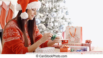 Young woman sitting wrapping Christmas gifts